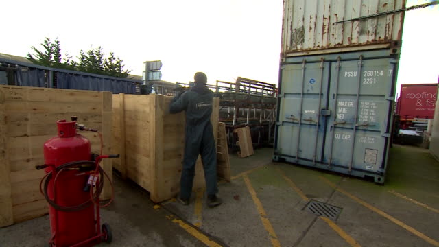 wide shot of two workers loading a wooden crate with construction material - イングランド南西部点の映像素材/bロール