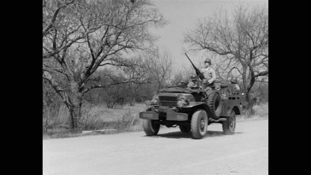 wide shot of us army soldiers driving jeep with machine gun on road - army stock videos & royalty-free footage