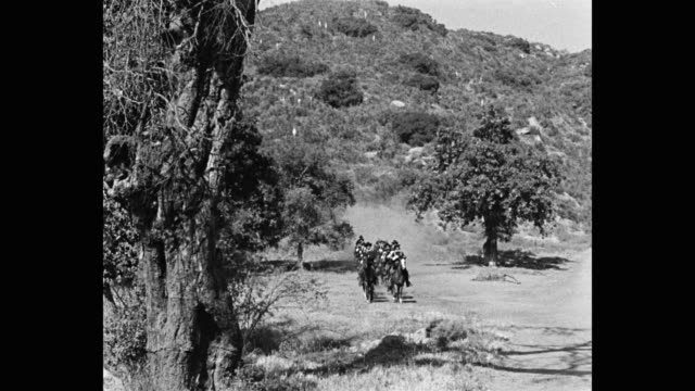 wide shot of us cavalrymen riding horses on dirt road - arbeitstier stock-videos und b-roll-filmmaterial