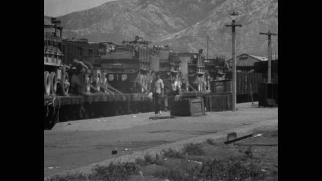 wide shot of us military vehicles loaded on freight train at railway platform - medium group of people stock videos & royalty-free footage