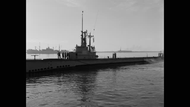 wide shot of us navy submarine moving towards harbor - surfacing stock videos & royalty-free footage