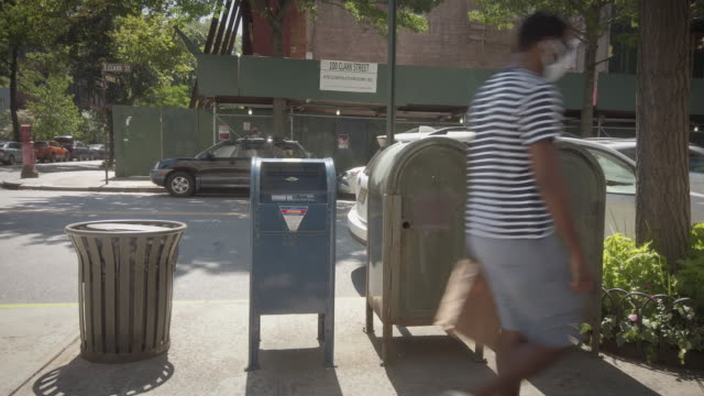wide shot of usps postal mail letter box on the street in brooklyn new york city man passing by with protective face mask filmed during the election... - brooklyn new york stock videos & royalty-free footage