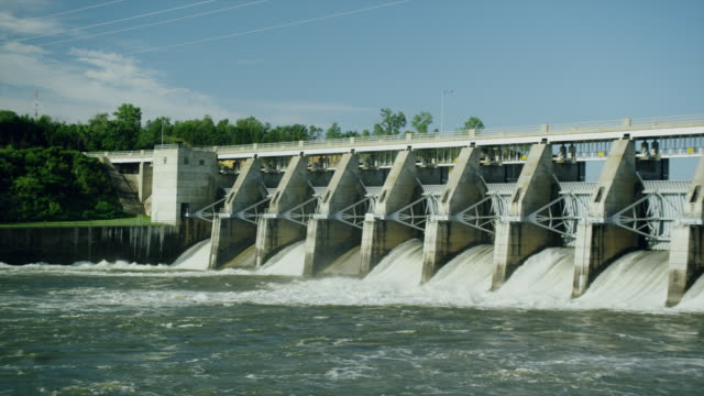 WIde shot of Water spillway behind electricity generating dam