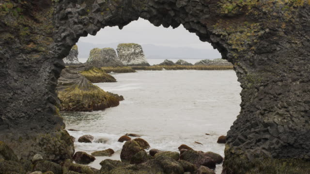 Wide shot of waves on beach near arch rock formation / Arnarstapi, Snaefellsnes, Iceland