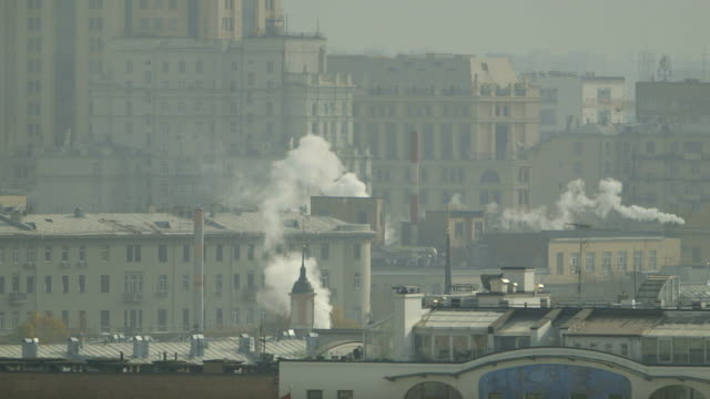 Wide shot of white smoke billowing from buildings in Moscow, Russia.