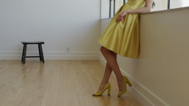 wide shot of woman in yellow dress leaning on window sill / draper, utah, united states - leaning stock videos and b-roll footage