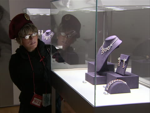 wide shot of woman looking at display of actor and philanthropist's elizabeth taylor jewels. these jewels were part of a four-day charity auction of... - auction stock videos & royalty-free footage