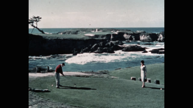 wide shot of woman looking at man playing golf by sea - golf swing stock videos & royalty-free footage