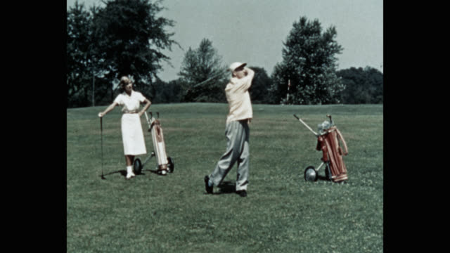 wide shot of woman looking at man playing golf on golf course - golf swing stock videos & royalty-free footage