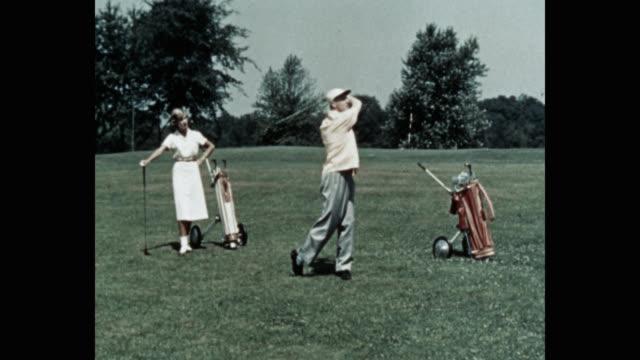 wide shot of woman looking at man playing golf on golf course - golf bildbanksvideor och videomaterial från bakom kulisserna
