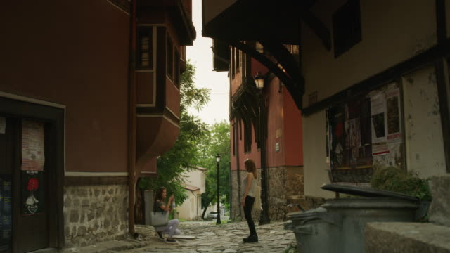 Wide shot of woman photographing friend in street / Plovdiv, Bulgaria