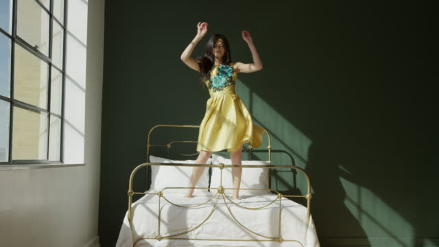 Wide shot of woman standing on bed near window and dancing / Draper, Utah, United States