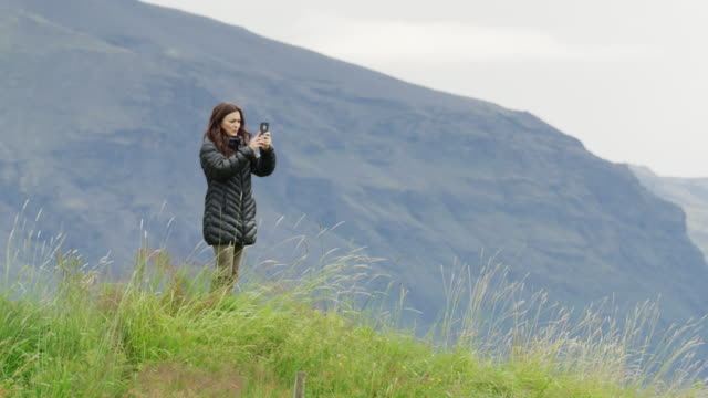 wide shot of woman turning and photographing scenic view / austur-skaftafellssysla, iceland - only mid adult women stock videos and b-roll footage