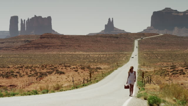 Wide shot of woman walking on roadside with gas can in Monument Valley / Highway 163, Monument Valley, Utah, United States,