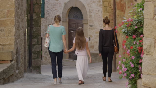 wide shot of women and girl walking in narrow street / montecello, tuscany, italy - narrow stock videos and b-roll footage