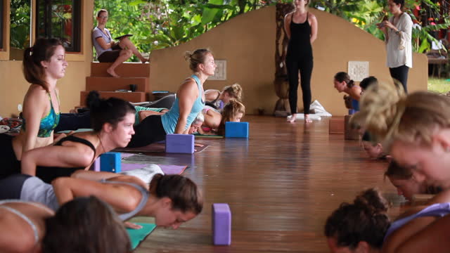 wide shot of women practising yoga on an outdoor yoga deck on colourful yoga mats and yoga blocks surrounded by lush vegetation - kelly mason videos stock videos & royalty-free footage