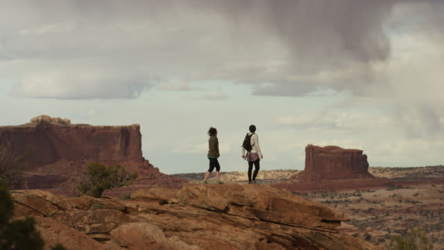 Wide shot of women standing on mountain with scenic view / Moab, Utah, United States