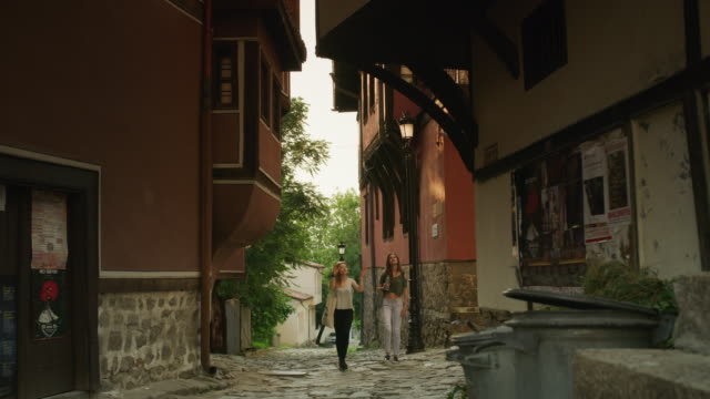 Wide shot of women walking and admiring architecture / Plovdiv, Bulgaria