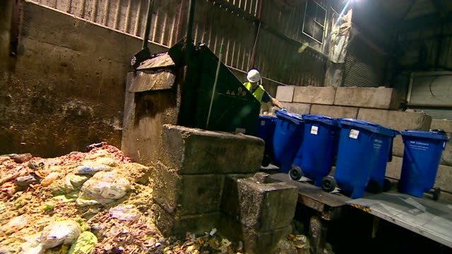 Wide shot of workers loading blue wheelie bins into reprocessing plant