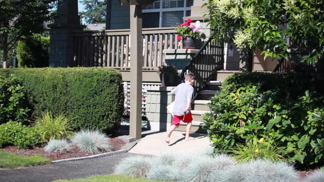 wide shot of young boy running along path and up stairs in upscale neighbourhood - kelly mason videos stock videos & royalty-free footage