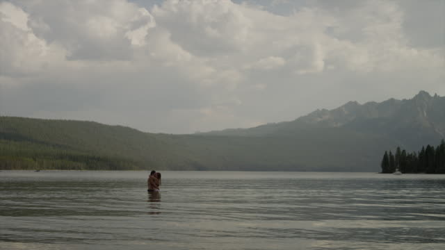 Wide shot of young couple hugging in lake / Redfish Lake, Idaho, United States