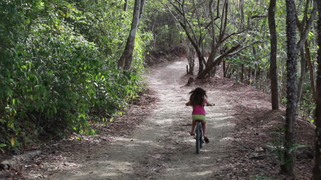 wide shot of young girl riding away from camera down a long windy country road - kelly mason videos stock videos & royalty-free footage