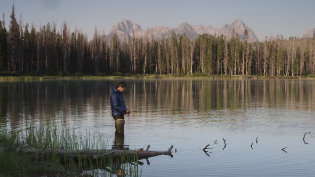 Wide shot of young man fly-fishing on lake with mountains in background / Redfish Lake, Idaho, United States