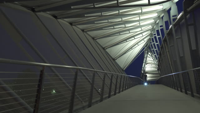 wide shot of young man passing through bridge using two-wheeled board - elevated walkway stock videos & royalty-free footage