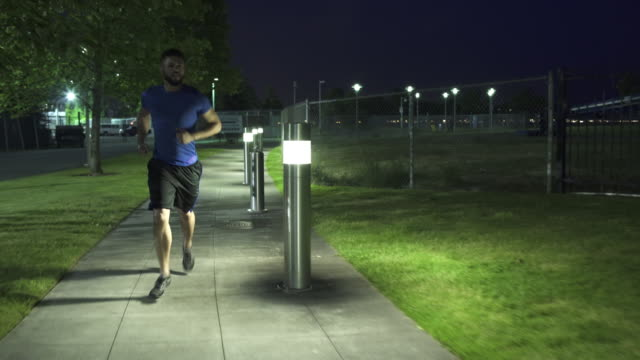 wide shot of young man running at night - electric lamp stock videos & royalty-free footage