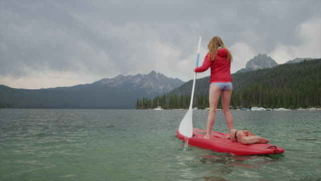 wide shot of young woman paddleboarding on lake / redfish lake, idaho, united states - ganzkörperansicht stock-videos und b-roll-filmmaterial