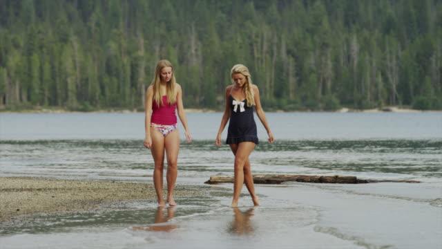 Wide shot of young women wading in lake / Redfish Lake, Idaho, United States