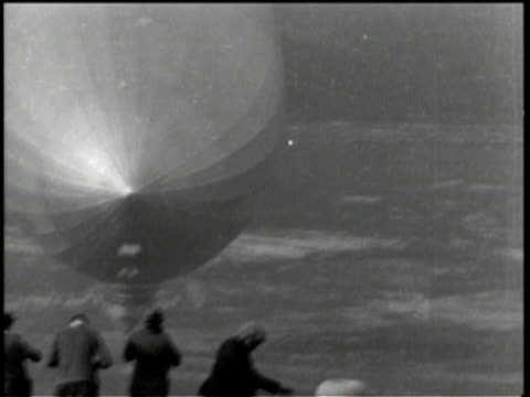 wide shot of zeppelin surround by people / the zeppelin floats across the ground and people move with it / military men are guiding the zeppelin with... - newsreel stock videos & royalty-free footage