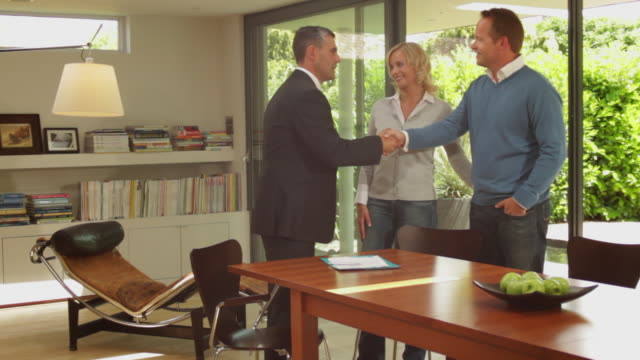 Wide shot off couple handshake with sales person in contemporary home
