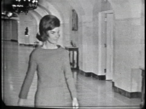 wide shot off sticks of jackie kennedy walking down a long, wide hallway. she is wearing a dress with long sleeves and she has short hair. it takes... - jackie kennedy stock videos & royalty-free footage