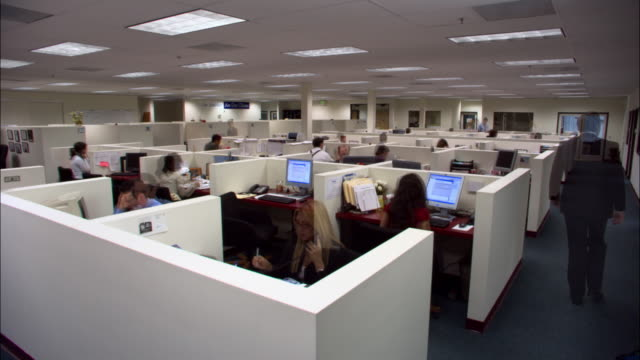 wide shot office workers working in cubicles / dissolve throughout day to last worker turning off light/ low angle - office partition stock videos & royalty-free footage