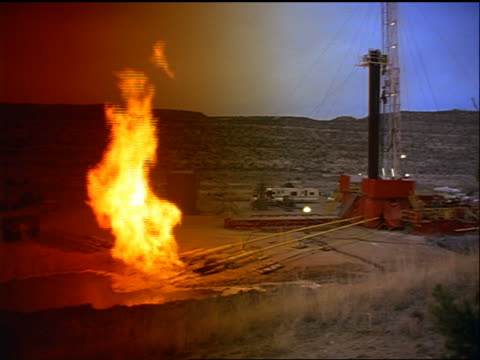 vídeos de stock, filmes e b-roll de wide shot oil/natural gas well / large burst of fire in foreground (gas released + torched off in pipe cleaning) - fire natural phenomenon