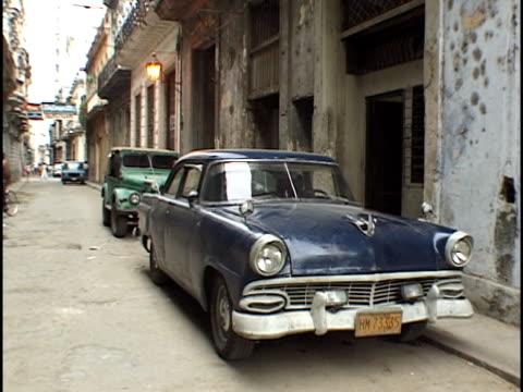 wide shot old cars on narrow street/ havana, cuba - enge stock-videos und b-roll-filmmaterial