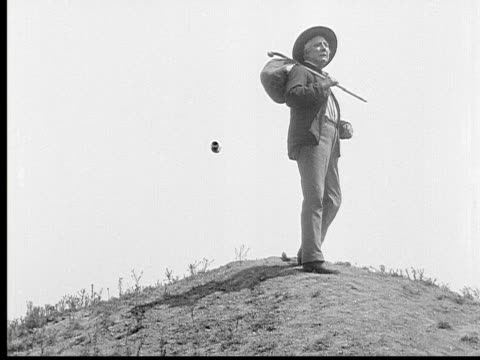 1913 b/w wide shot old man carrying knapsack and cane stands atop hill during journey / usa  - loneliness stock videos and b-roll footage