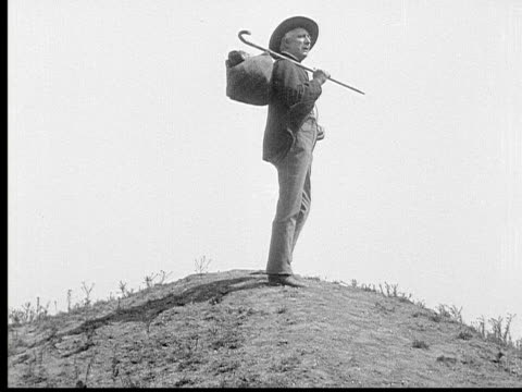 vídeos de stock e filmes b-roll de 1913 b/w wide shot old man carrying knapsack and cane stands atop hill during journey / usa  - loneliness