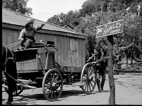 1913 b/w wide shot old man with knapsack and cane getting off horse cart, talking to driver, and pointing to sign reading 'to hawley center' / usa  - horse cart stock videos and b-roll footage