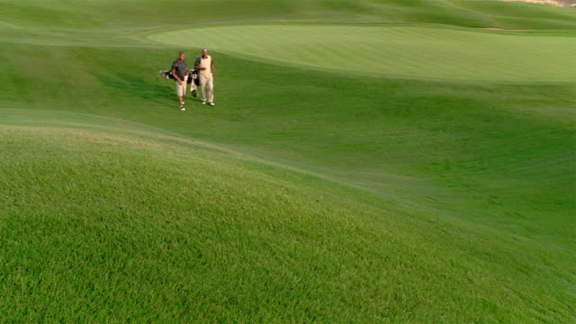 wide shot older man and younger man walking on golf course toward camera - golf shoe stock videos & royalty-free footage