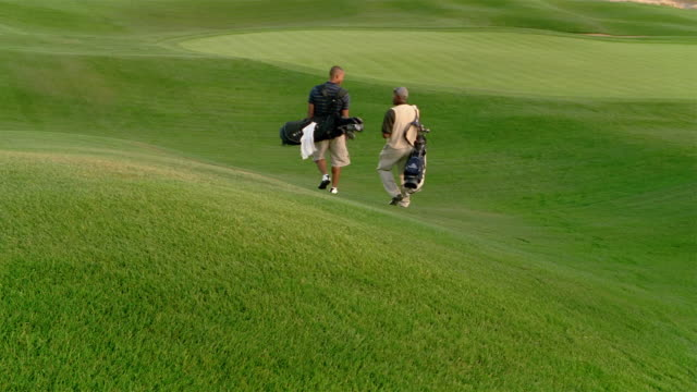 wide shot older man and younger man walking on golf course - golf shoe stock videos & royalty-free footage