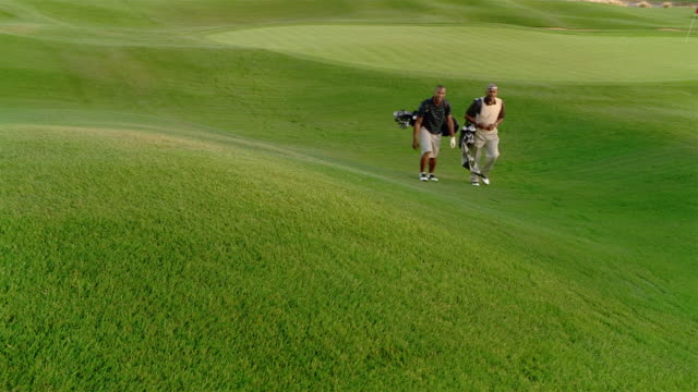 wide shot older man and younger man walking toward camera carrying golf bags / medium shot men climb hill - golf shoe stock videos & royalty-free footage