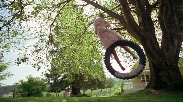 wide shot one girl pushing another on tire swing near house / des moines, king county, washington, usa - tyre swing stock videos & royalty-free footage