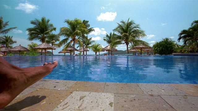 Wide shot outdoor swimming pool with palms trees in background / man diving in pool
