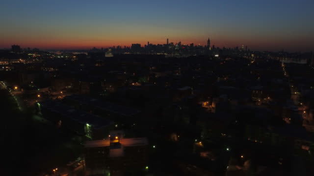 wide shot over dark streets in hoboken, panning right with new york city skyline in distance at sunrise - low stock videos & royalty-free footage