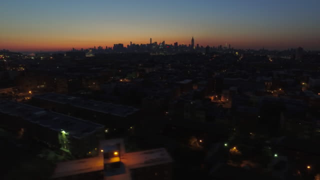 Wide shot over dark streets in Hoboken, panning right with New York City skyline in distance at sunrise