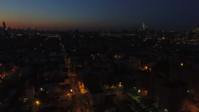 Wide shot over dark streets in Hoboken with dark pink sunrise and One World Trade Center at right of frame