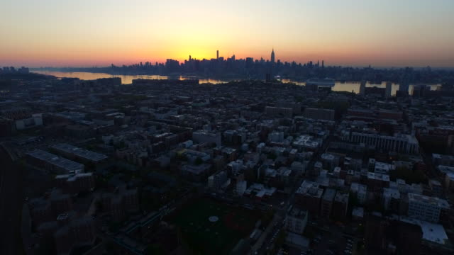 Wide shot over Hoboken, across Hudson River to New York City skyline at sunrise
