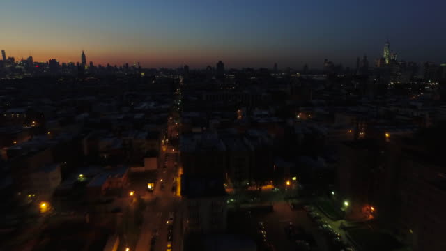 wide shot over hoboken, pulling away from new york city skyline in distance at sunrise - dark stock videos & royalty-free footage